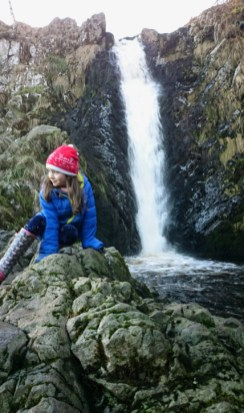 Image of girl-in-blue-anorak-and-red-hat-hitting-on-rocks-with-waterfall-behind