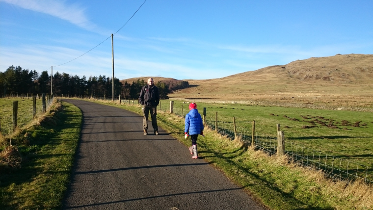 Image of man-and-girl-walking-along-road-in-hills
