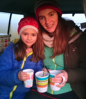 Image of woman and-child-wearing-winter-outdoor-gear-in-vehicle-holding-mugs