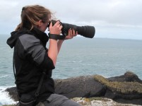 Image of woman-on-rocks-overlooking-sea-taking-photo-with-large-zoom-lens-camera