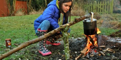 Image of girl-looking-at-pot-cooking-on-camp-fire-in-garden