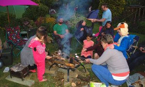Image of group-of-people-and-children-around-firepit-in-garden
