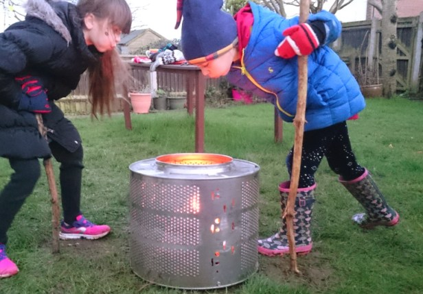 two-girls-blowing-flames-of-fire-in-washing-machine-drum-in-a-garden
