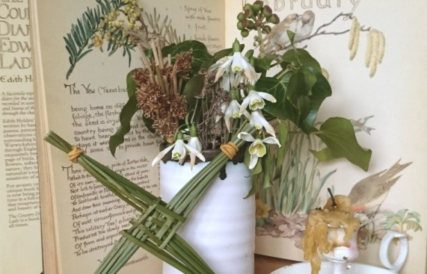 Image of vase-of-snowdrops-with-candle-and-brigids-reed-cross