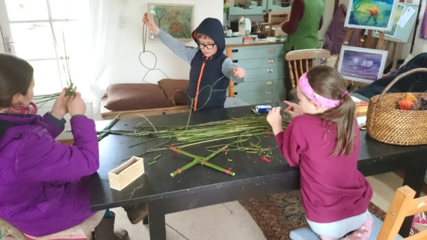 woman-and-children-working-with-reeds-at-a-table
