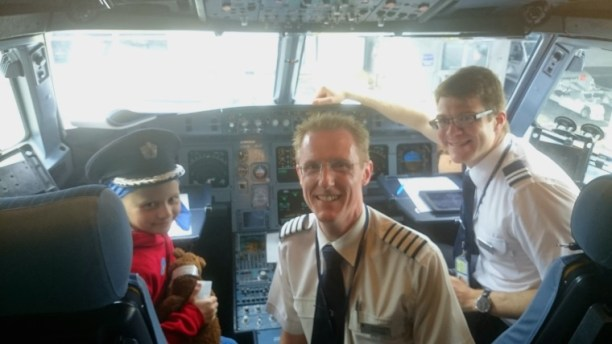 Image of girl in pilot's hat with 2 pilots in BA aircraft cockpit