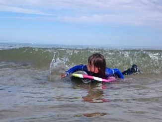 Image of girl in wetsuit on body board surfing a small wave