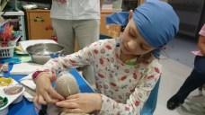 Image of girl pressing plastic fibre around teddy bear's head