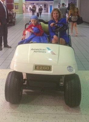 Image of woman and girl on airport luggage buggy