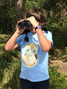 Image of Boy in woods with binoculars