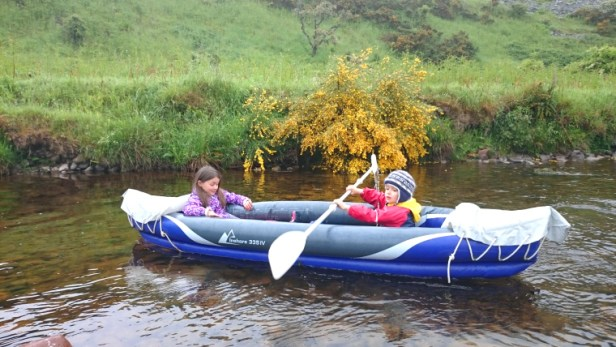 Children in inflatable canoe on river