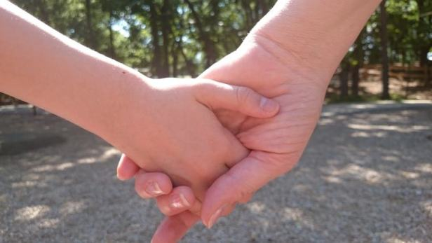 Close up of woman and child holding hands in sunshine