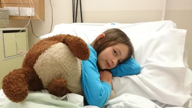 Girl and brown teddy bear lying in hospital bed