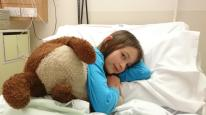 Image of girl and brown teddy bear lying in hospital bed