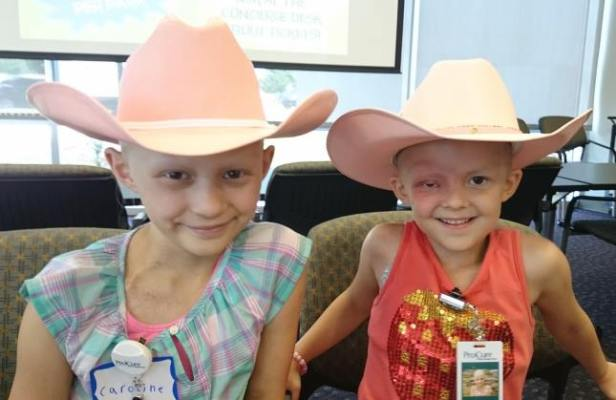 Two young cancer patients with no hair in cowboy hats