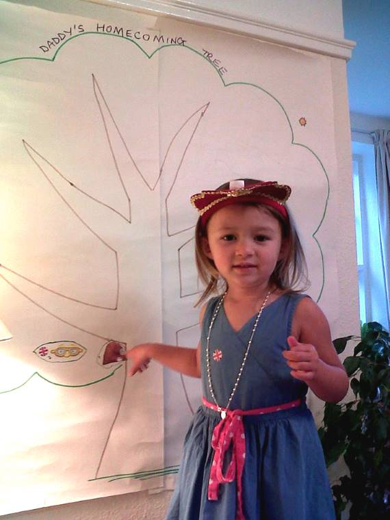 Toddler in blue dress pointing to stickers on wall mural of tree outline