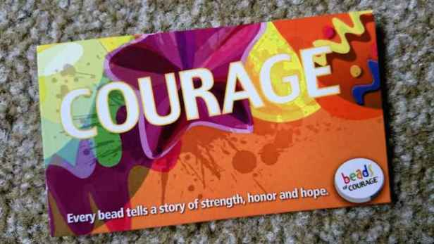 Close up image of brightly coloured information card with 'Courage' in large letters on red background