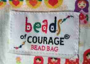 Close up image of cloth label with words Beads of Courage Bead Bag written on