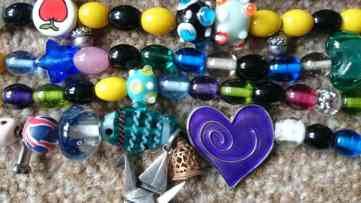 Close up image of glass and metal beads with purple heart, fish, acorns and apple plus plain beads