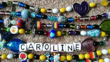 Close up image of string of multicoloured glass beads in name Caroline with hearts and metal beads