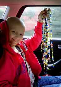 Image of smiling girl in pink cardigan sitting in car seat holding up string of mulitcoloured glass beads