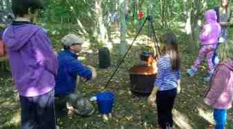 Image of children gathered around a cooking pot hanging over a camp fire in the woods