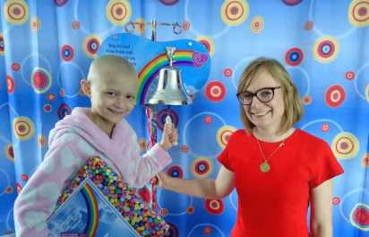Image of girl in dressing gown ringing bell on a stand with woman in red dress and bright patterned hospital curtains behind