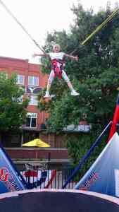 Image of girl with no hair doing star jump on open air bungee trampoline