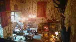 Image of people at small tables in medieval stone walled room with flags, pikes, antlers and open fire decorating walls