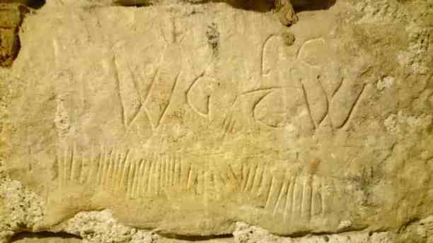 Image of scratched initials and markings in ancient stone wall