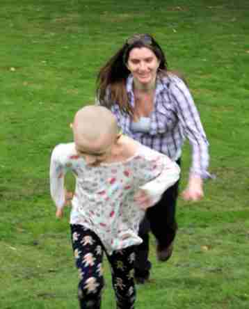 Image of smiling woman racing child with no hair on grass