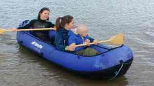 Image of two women and girl in blue inflatable kayak in sea