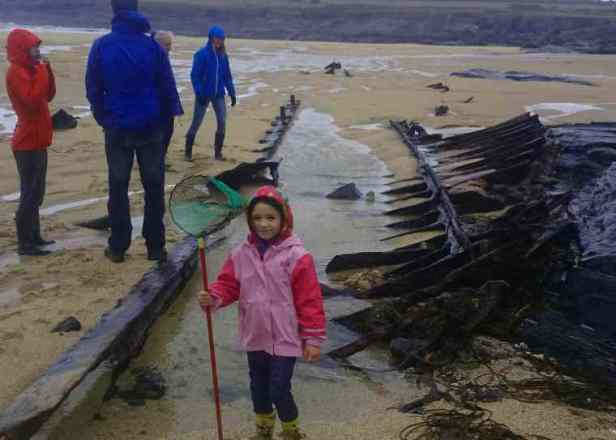 Image of girl with fishing net and adults investigating iron shipwreck on rainy beach