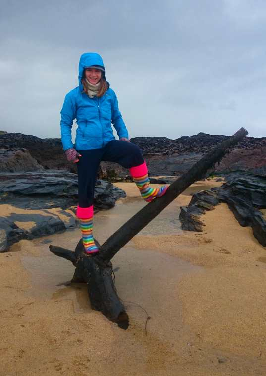 Image of woman in rain gear standing on top of iron mast head of shipwreck buried in sand