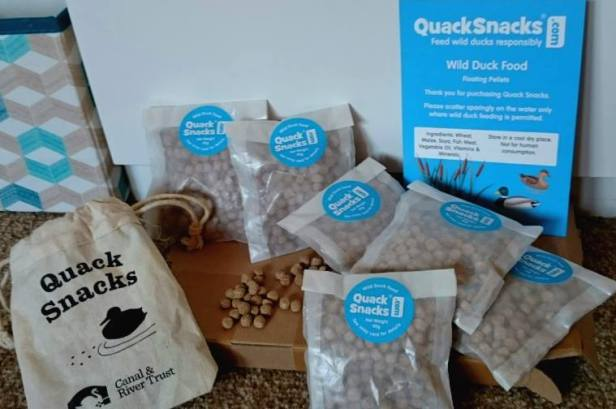Image of cardboard packet with small packets of pellets, a hessian pouch with Quacksnacks and Canal Trust written on plus blue marketing sheet for Quacksnacks