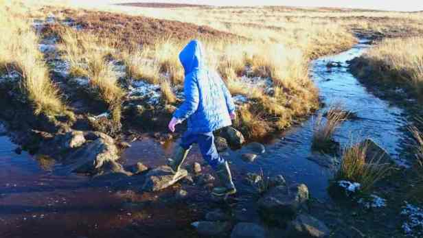 Image of child in blue coat, wellies and black hat crossing stepping stones over stream on moorland