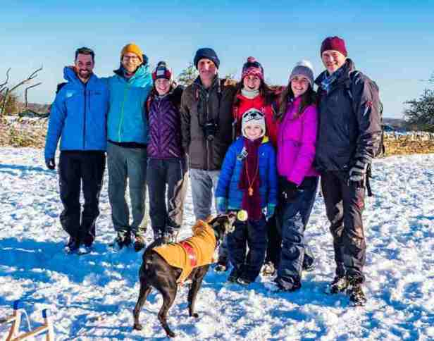 Image of family group in snow with black dog at front throwing his own snowball