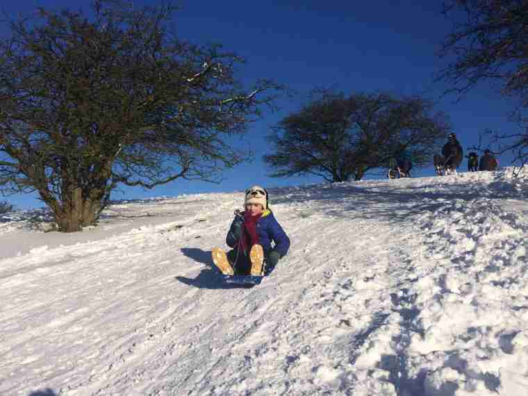 Image of girl in blue coat and white hat riding sledge on snowy hill with gorgeous blue sky