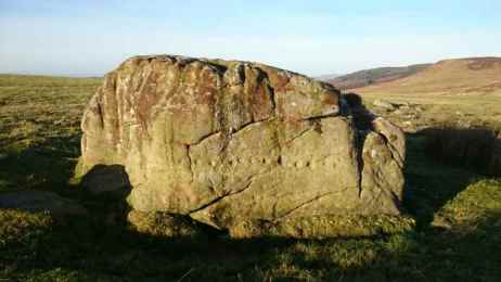 Image of large rectangular rock with several cound carvings in the side with moorland views behind