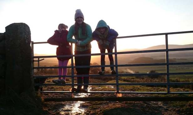 Image of silhouette of woman and two children and dog in sunset standing on metal gate with hill view behind