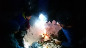 Image of two men and a girl in dark around a camp fire with windbreak of snow round fire