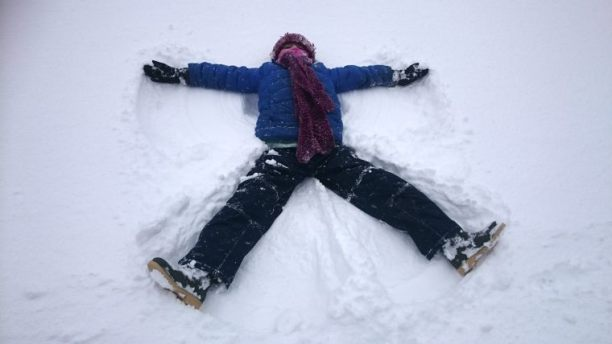 Image of child making an angel pattern in the snow