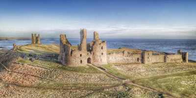 Image of Dunstanburgh Castle from the air with frosty grass in foreground and sea behind