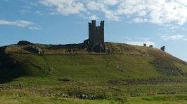 Image of Dunstanburgh castle tower ruin on steep outcrop of rock from west side