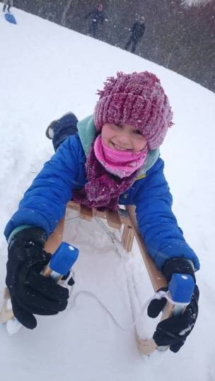 Image of girl in blue coat and burgundy hat and scarf covered in snow on a sledge head first