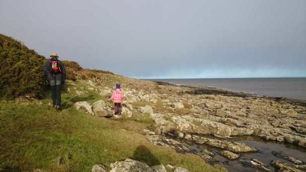 Image of man and child in outdoor gear walking on grassy coastline with rocky beach and sea in background