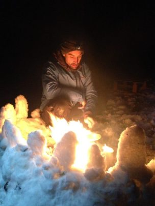 Image of man in blue jacket lighting a camp fire outdoors at night behind a windbreak of snow