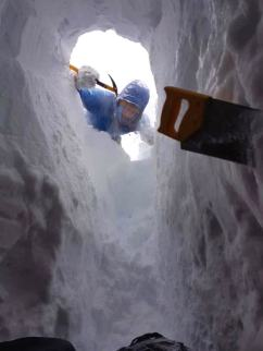 Image of man in blue snow gear holding ice axe looking down from entrance to snow hole into tunnel with saw embedded in snow wall