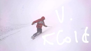 Image of man in red ski jacket in deep snow checking depth with a long stick with the words V Cold arrowing towards the man