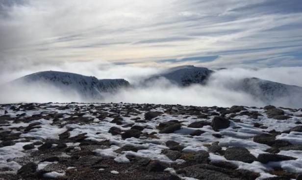 Image of mountain ridge appearing through cloud with snow and rock in foreground
